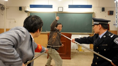 Chinese policemen show teachers and school workers how to defend themselves during an attack at a school in Beijing on April 2010.