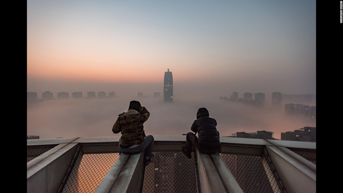 "Photographers view heavy smog from the roof of a building in Zhengzhou, China, on Tuesday, January 3. China <a href=""http://www.cnn.com/2017/01/03/asia/china-fog-alert/"" target=""_blank"">issued its first-ever red alert for fog</a> in a number of northern and eastern regions. That followed some 24 cities issuing red alerts for air pollution. Red is the most serious level in the country's warning system."
