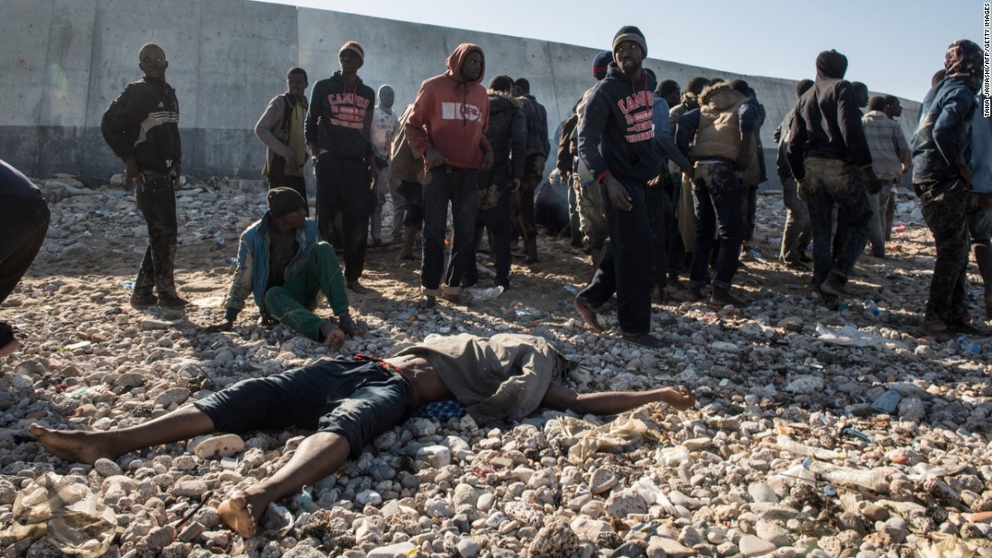 "Migrants stand next to a dead body after their boat washed ashore in Tripoli, Libya, on Wednesday, January 4. The migrants, mostly from Senegal, had left Sabratha, Libya, hoping to reach Europe. They spotted land and thought it was Italy, and several drowned trying to swim to shore. <a href=""http://www.cnn.com/2015/09/03/world/gallery/europes-refugee-crisis/index.html"" target=""_blank"">Europe's migration crisis in 25 photos</a>"