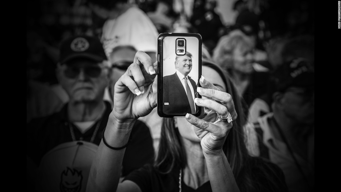 A woman takes a photo with a Trump-themed phone case during a rally in Los Angeles in September 2015.