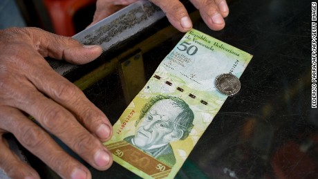 A man compares a new 50-Bolivar-coin with a Bolivar-note of the same denomination at a kiosk in Caracas on December 28, 2016.   Venezuela took delivery on December 27 of its third load of new, bigger denomination banknotes, its central bank said, but there was no sign of them in circulation yet despite official promises and mounting public anxiety. Maduro's announcement that the 100-bolivar notes would suddenly no longer be legal tender provoked long lines of people trying to change them, and looting and rioting in some areas, resulting in four deaths. / AFP / FEDERICO PARRA        (Photo credit should read FEDERICO PARRA/AFP/Getty Images)