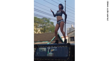 Another pole dancer performing on top of a Jeep.