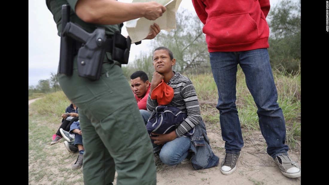 A US Border Patrol agent checks birth certificates while taking Central American immigrants into custody in McAllen, Texas, on Wednesday, January 4.<br />
