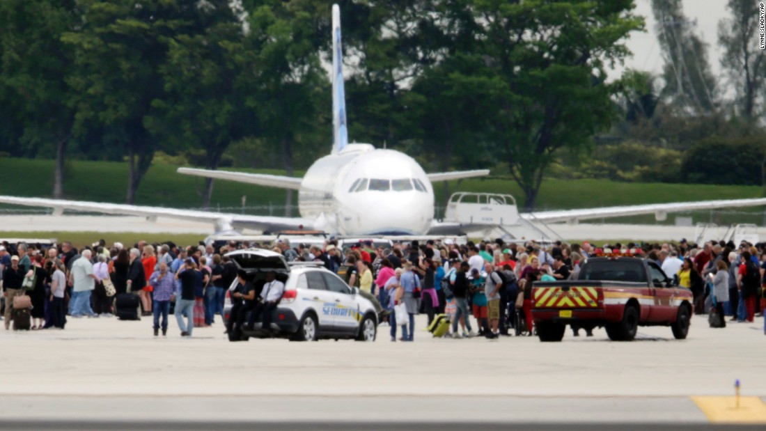 People stand on the tarmac at Fort Lauderdale-Hollywood International Airport after a gunman opened fire inside Terminal 2 on Friday, January 6.