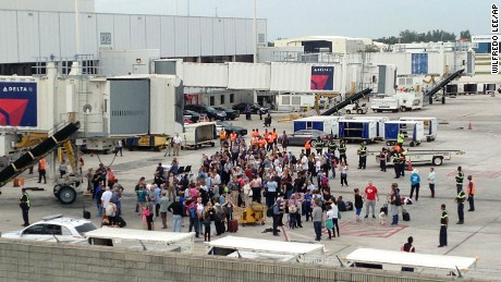 People stand on the tarmac at the Fort Lauderdale-Hollywood International Airport after a shooter opened fire inside a terminal of the airport, killing several people and wounding others before being taken into custody, Friday, January 6 in Fort Lauderdale, Florida.