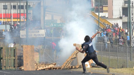 A police officer throws a stone at demonstrators protesting against the rise of fuel prices, in Puebla, Mexico, on January 6, 2017. The death toll in protests against a gasoline price increase in Mexico rose to three on Friday as two men died of gunshot wounds after a clash with police. The clash followed days of nationwide demonstrations, highway blockades and looting that began when the government hiked gasoline prices by 20.1 percent on January 1. / AFP / Jose CASTANARES        (Photo credit should read JOSE CASTANARES/AFP/Getty Images)