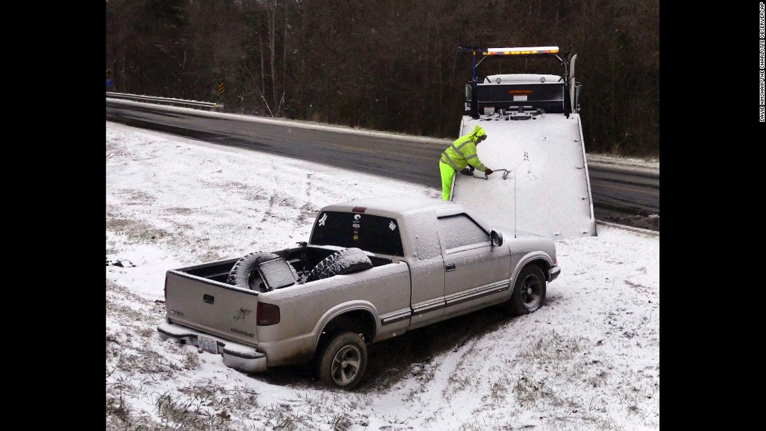 Mark Blackwell with Bradley Wrecker Service pulls a truck from a ditch near Charlotte Douglas International Airport early on January 7 after the storm dumped several inches of snow across parts of North Carolina.