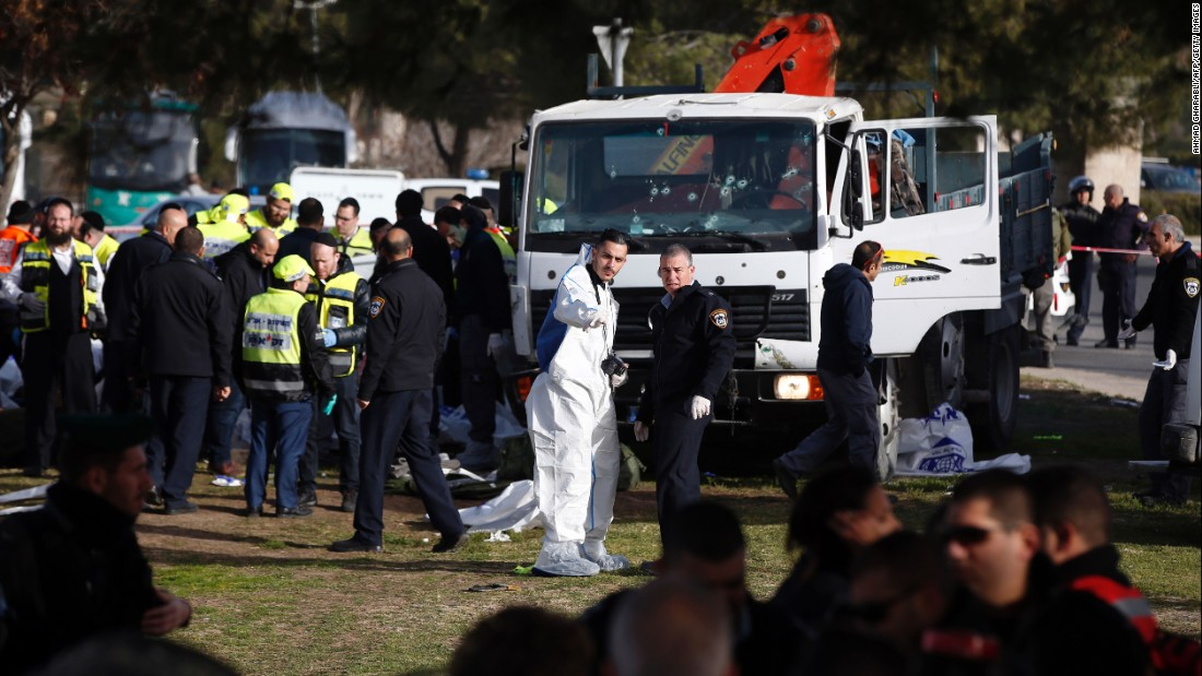 Israeli security forces and emergency personnel gather at the site of the vehicle attack. The attacker was shot and killed; note the bullet holes in the truck's windshield.