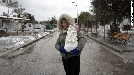 A girl holds a snowman at the Kara Tepe camp on the Greek island of Lesbos following heavy snow.
