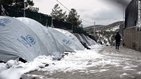 An asylum seeker walks next to snow-covered tents at the Moria refugee camp.