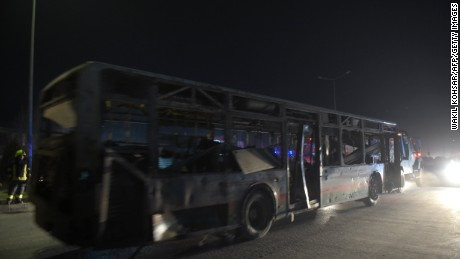 Security forces remove a damaged bus after Tuesday's blasts near the Afghan parliament in Kabul.
