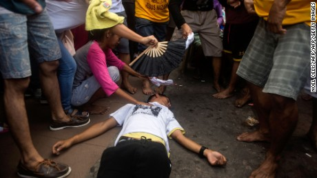 A devotee collapses during the procession to Quiapo Church along a road in Manila.