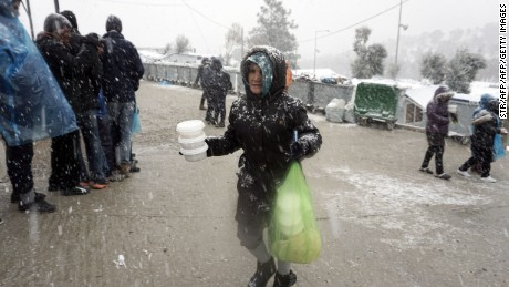 A migrant receives food during snowfall at the Moria camp on Lesbos, on January 9, 2017.