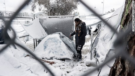 A migrant stands next to a snow-covered tent at the Moria refugee camp, Lesbos.