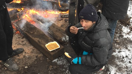After they receive food from aid agencies once a day, migrants warm it up by the open fires they light by burning, wood, scraps, or any other material they can get their hands on.