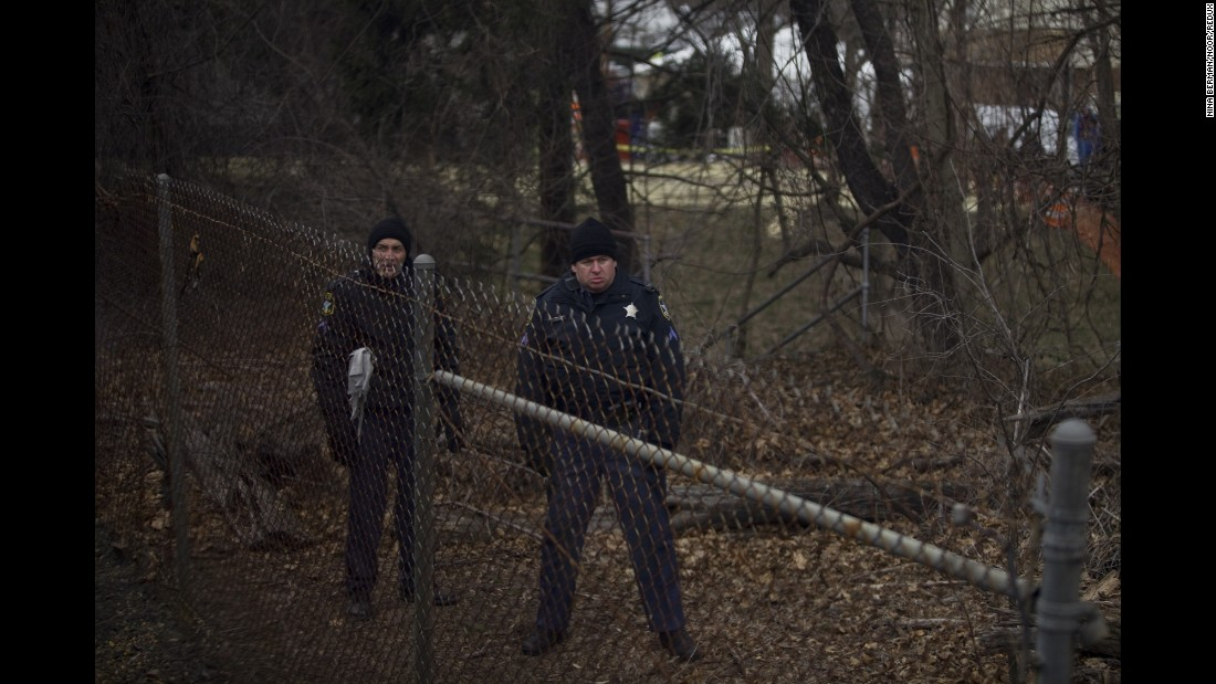 Police officers watch from behind a fence.
