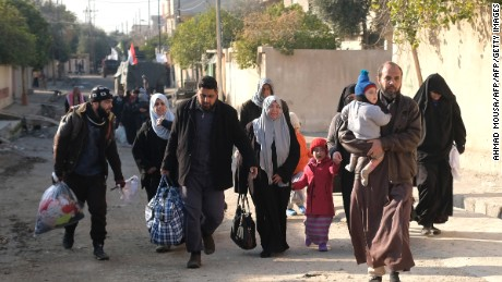 Iraqi civilians fleeing their neighbourhoods due to the ongoing fighting with Islamic State (IS) group jihadists arrive to the northern edge of al-Mithaq neighbourhood in southeastern Mosul, on January 4, 2017.