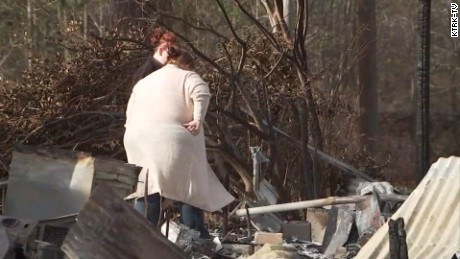 Wray and her daughter Cassidy look on at the damage caused by the fire.  They own the land where the house is and are planning to rebuild.
