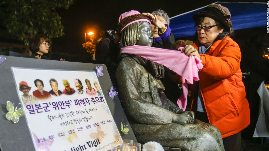 Supporters place a scarf and hat on the Glendale memorial statue during a candlelit vigil in January 2016.