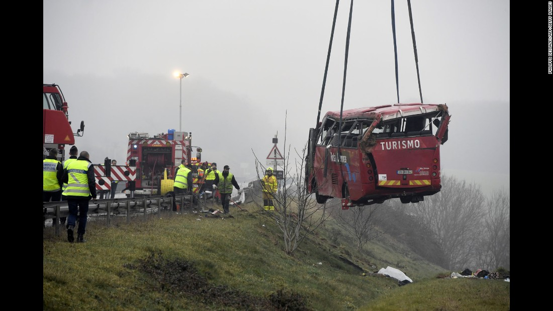 Rescue workers stand near a bus that crashed off a highway near Charolles, France, on Sunday, January 8. Four Portuguese tourists were killed in the crash, authorities said.