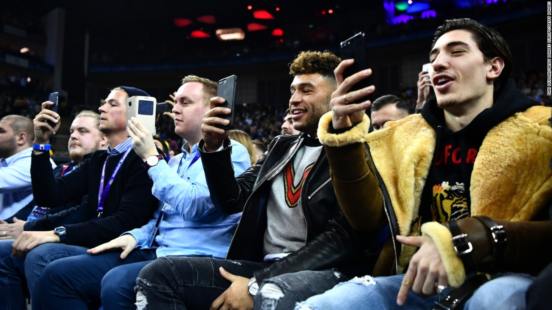 Arsenal footballers Hector Bellerin (right) and Alex Oxlade-Chamberlain snap shots of Thursday's NBA clash between the Nuggets and the Pacers at London's O2 Arena.