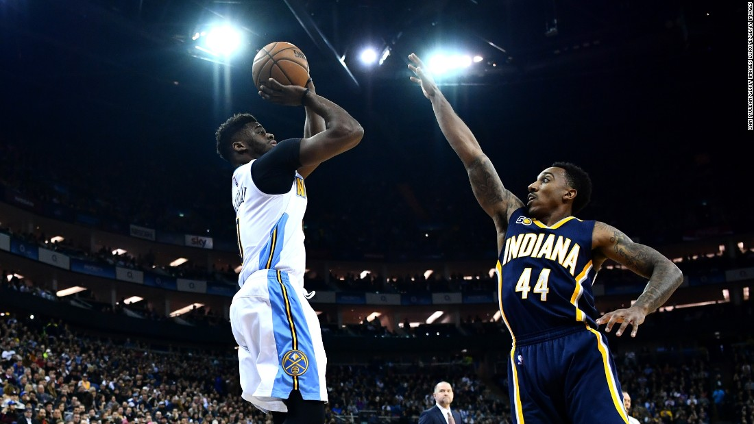 Pacers' Jeff Teague tries to block Emmanuel Mudiay of the Nuggets under the lights of London's O2 Arena.