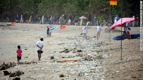 Foreign tourists and locals alike walk along the popular Kuta beach covered with debris and rubbish washed up by the tide, near Denpasar on the resort island of Bali.