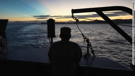 "GUANTANAMO BAY, CUBA - OCTOBER 24:  (EDITORS NOTE: Image has been reviewed by the U.S. Military prior to transmission.) A U.S. soldier looks towards the first rays of sunlight while on a dawn ferry near the military prison known as ""Gitmo"" on October 24, 2016 at at the U.S. Naval Station at Guantanamo Bay, Cuba. The U.S. military's Joint Task Force Guantanamo is holding 60 detainees at the prison, down from a previous total of 780. In 2008 President Obama issued an executive order to close the prison, which has failed because of political opposition in the U.S.  (Photo by John Moore/Getty Images)"