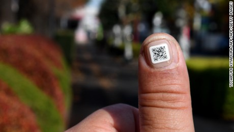 This picture taken on December 5, 2016 shows a city officer displaying a QR code on his fingernail near the Iruma city hall in Iruma, Saitama prefecture, a western suburb of Tokyo. A Japanese city has introduced a novel way to keep track of senior citizens with dementia who are prone to getting lost -- tagging their fingers and toes with scan-able barcodes. A company in Iruma, north of Tokyo, developed tiny nail stickers, each of which carries a unique identity number to help concerned families find missing loved ones, according to the city's social welfare office / AFP / Toshifumi KITAMURA        (Photo credit should read TOSHIFUMI KITAMURA/AFP/Getty Images)