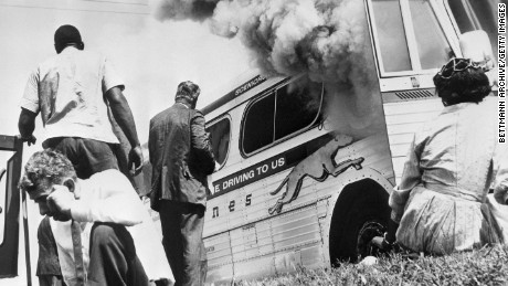 "Passengers of this smoking Greyhound bus, some of the members of the ""Freedom Riders,"" a group sponsored by the Congress of Racial Equality (CORE), sit on the ground after the bus was set afire 5/14/1961, by a mob of Caucasians who followed the bus from the city. The mob met the bus at the terminal, stoned it & slashed the tires, then followed the bus from town."