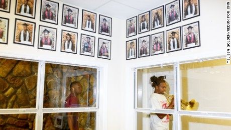 Portraits of graduates line the walls of the band director's office.