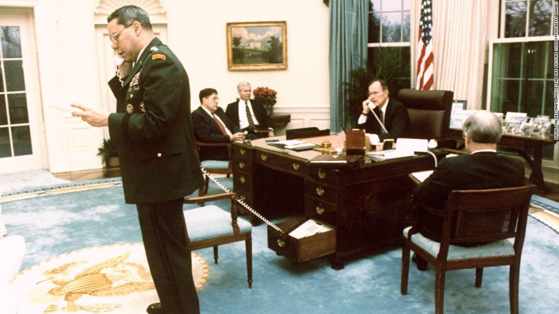 Chairman of the Joint Chiefs of Staff Colin Powell and Bush speak on separate phones in February 1991 while Joint Chiefs John Sununu, Robert Gates and Brent Scowcroft listen in to a conversation about halting the ground war in Saudi Arabia.