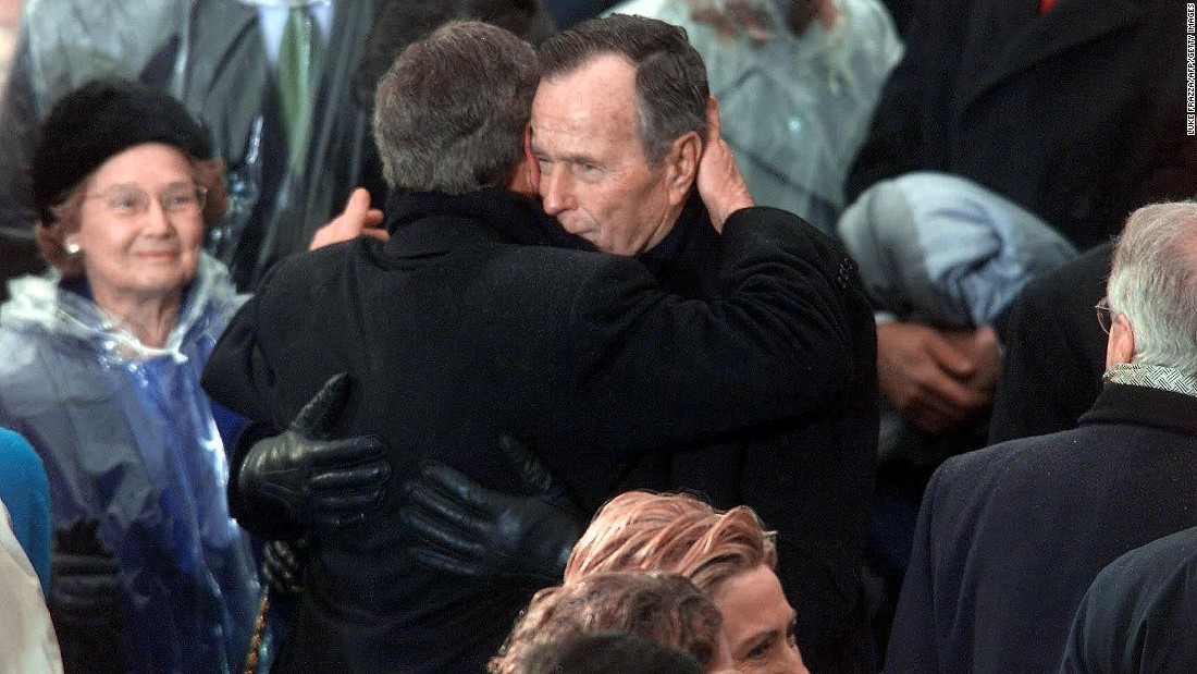 George H.W. Bush hugs his son, President George W. Bush, moments after the younger Bush was sworn in on January 20, 2001.