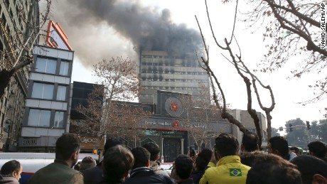 Iranians watch the Plasco building where smoke rises from its windows in central Tehran, Iran, Thursday, Jan. 19, 2017.