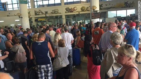Tourists gather at the Banjul airport Wednesday as tour operators send in extra flights for evacuation.