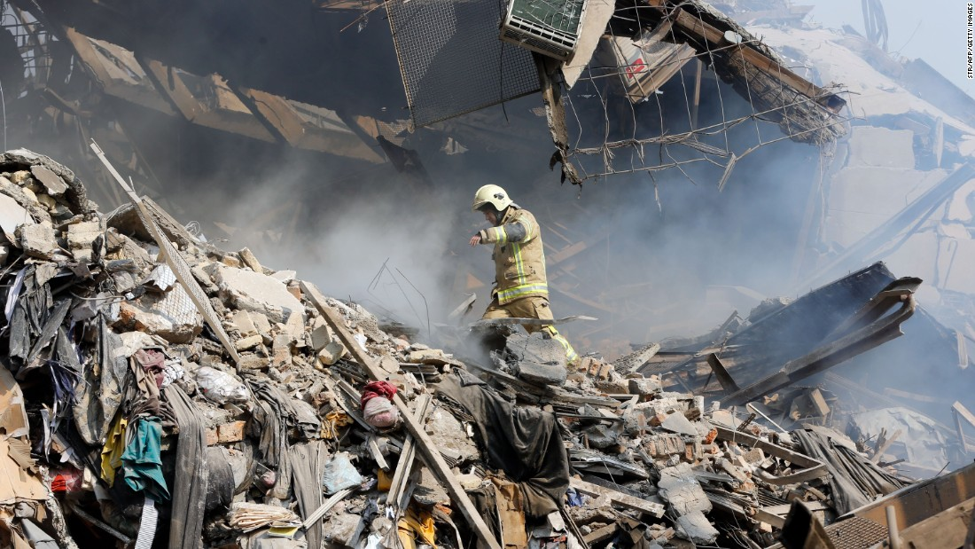 A firefighter climbs over the fallen wreckage of the Plasco building. Thirty-five firefighters are missing after the multi-story building collapsed around them as they battled a blaze, Tehran Fire Department spokesman Jalal Maleki told a local journalist on the scene. Rescue teams are trying to dig out the missing firefighters, Maleki said.