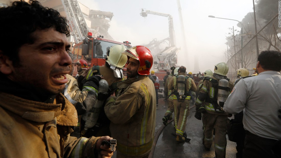 A firefighter reacts outside the building, where the blaze burned through the upper stories for more than three hours before the structure came down.