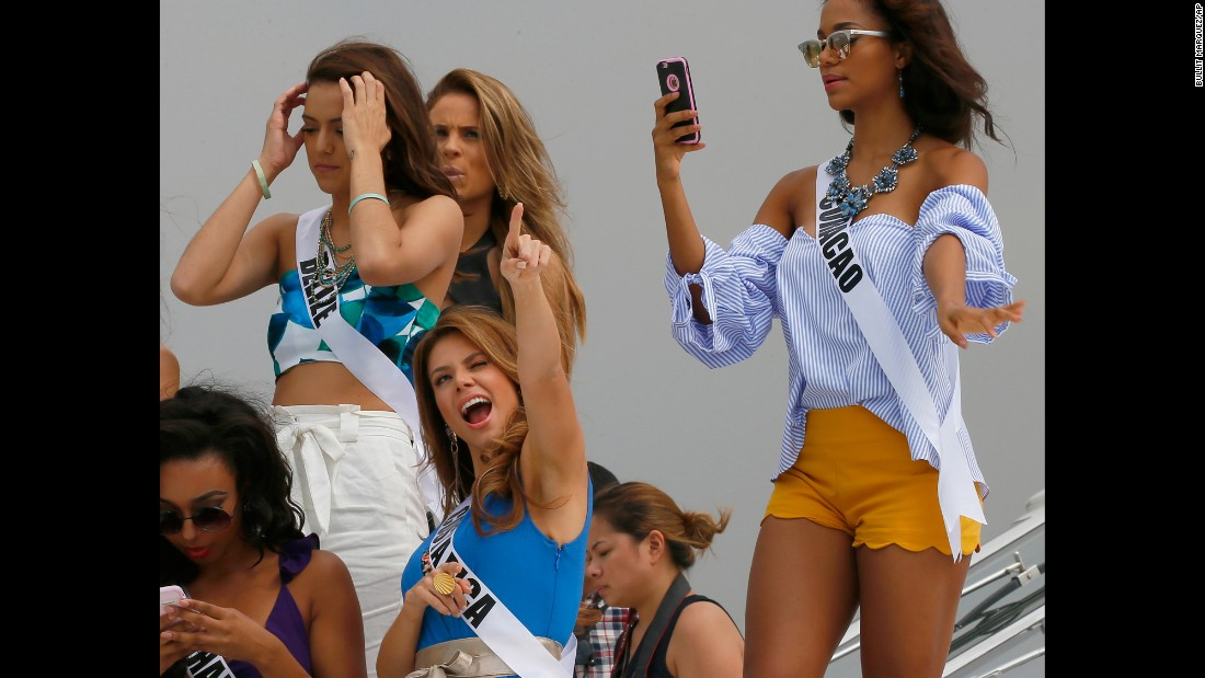 Miss Universe contestant Carolina Duran of Costa Rica, center, reacts to a TV network's drone while on a yacht in Manila, Philippines, on Thursday, January 19.