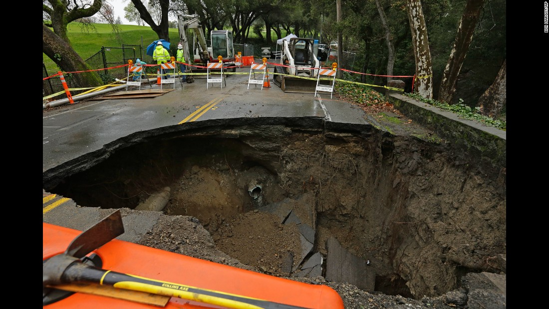 Workers survey a 72-inch diameter sinkhole in Orinda, California, on Wednesday, January 18. The city council of Orinda declared a state of emergency on Tuesday night because of the large sinkhole, which was caused by days of heavy rain in the area.
