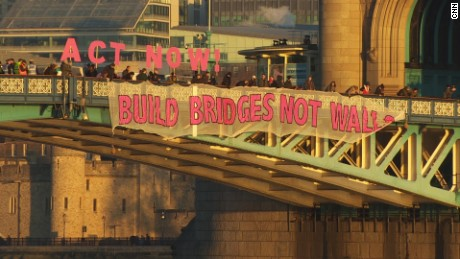 "A ""Bridges Not Walls"" banner hangs from London's Tower Bridge on Friday."