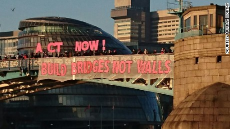 "Protesters hold ""Bridges Not Walls"" signs on Tower Bridge in London on January 20, 2017. ""It's a shared message of solidarity and hope against extremism, division and the rise of the political right around the world,"" said Murray Worthy, who shot this photo."