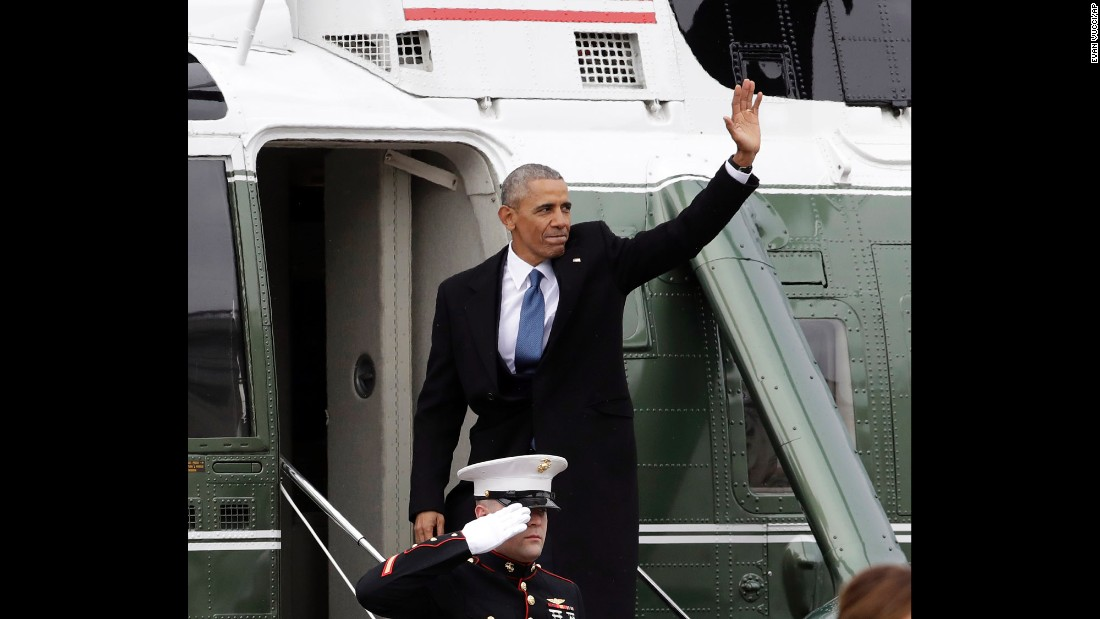 Former President Barack Obama waves as he boards a Marine helicopter during a departure ceremony.
