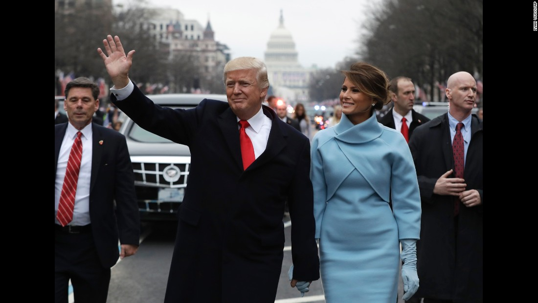 President Donald Trump waves as he walks on Pennsylvania Avenue with first lady Melania Trump during the Presidential Inaugural Parade on Friday, January 20.