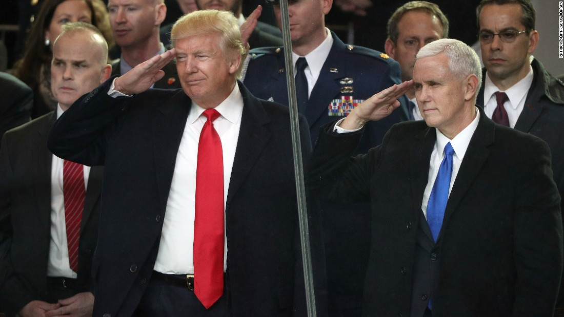 President Donald Trump and Vice President Mike Pence salute military personnel from the main reviewing stand in front of the White House during the Presidential Inaugural Parade.