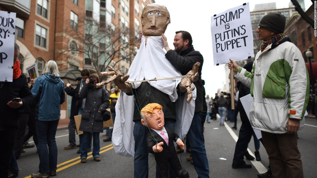 Protesters march with puppets depicting Trump and  Russian President Vladimir Putin.
