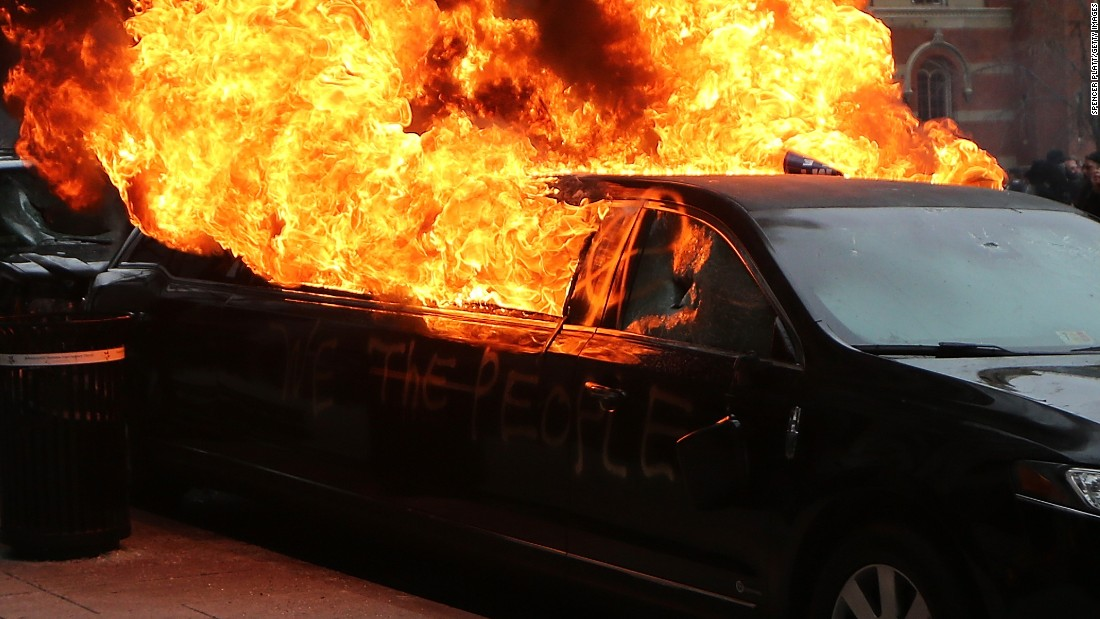 Flames erupt from a limousine after windows were smashed.