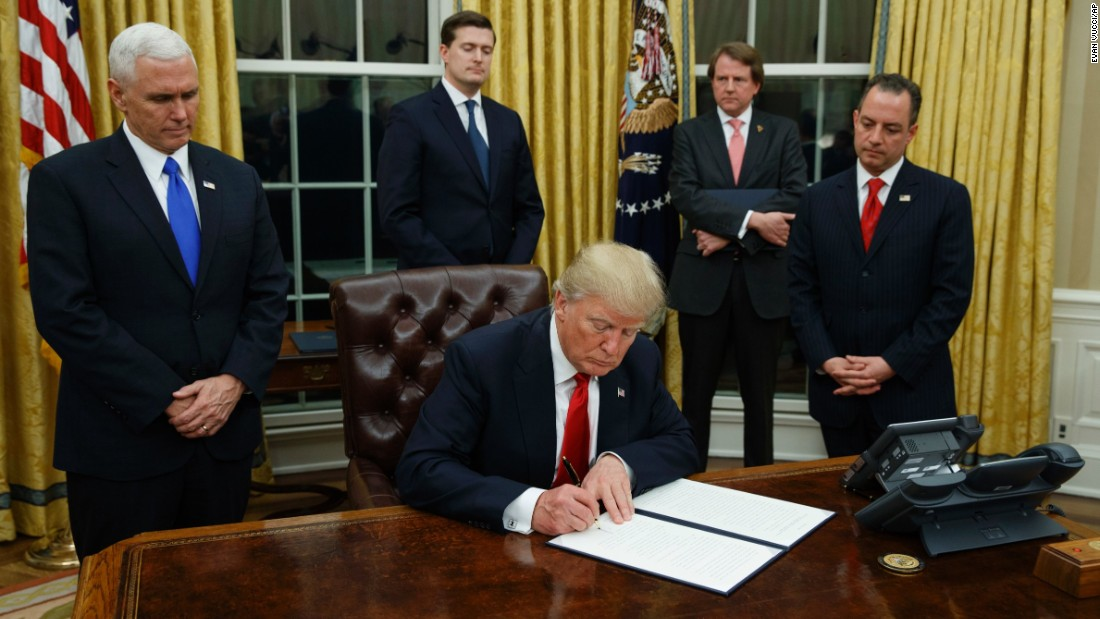 President Donald Trump, flanked by Vice President Mike Pence and Chief of Staff Reince Priebus, signs his first executive order on health care, Friday, January 20, in the Oval Office of the White House in Washington.
