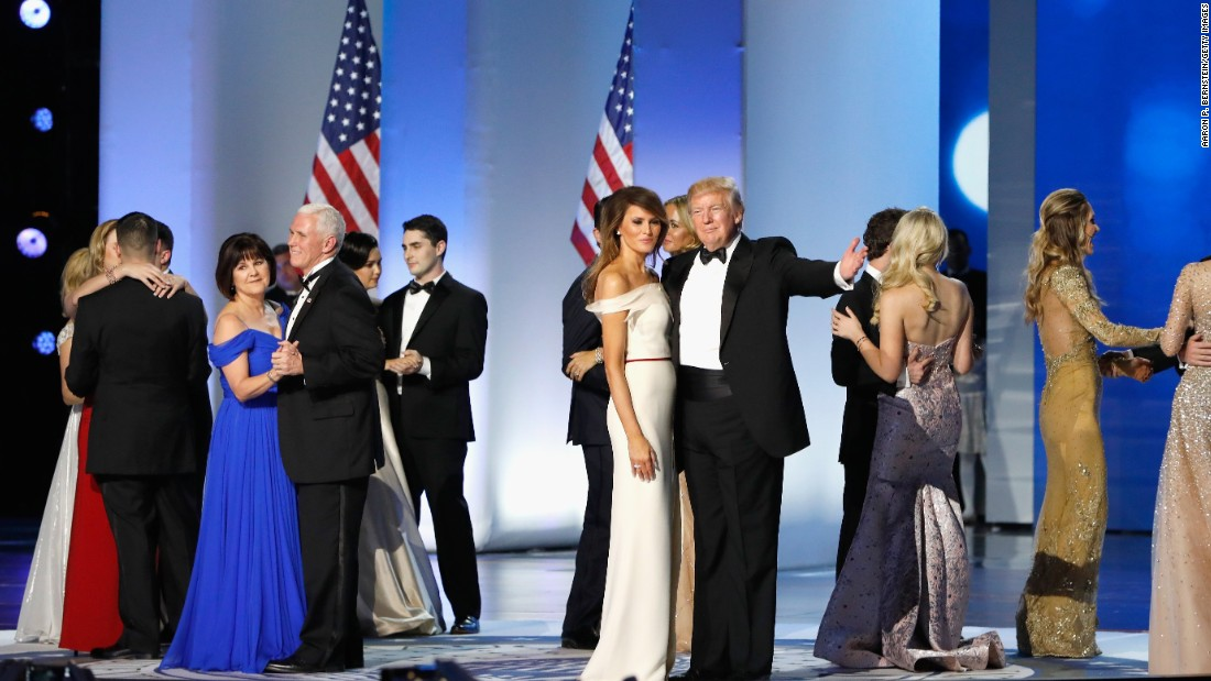 President Donald Trump, first lady Melania Trump, Vice President Mike Pence and his wife Karen dance with their families on stage at the Freedom Ball.