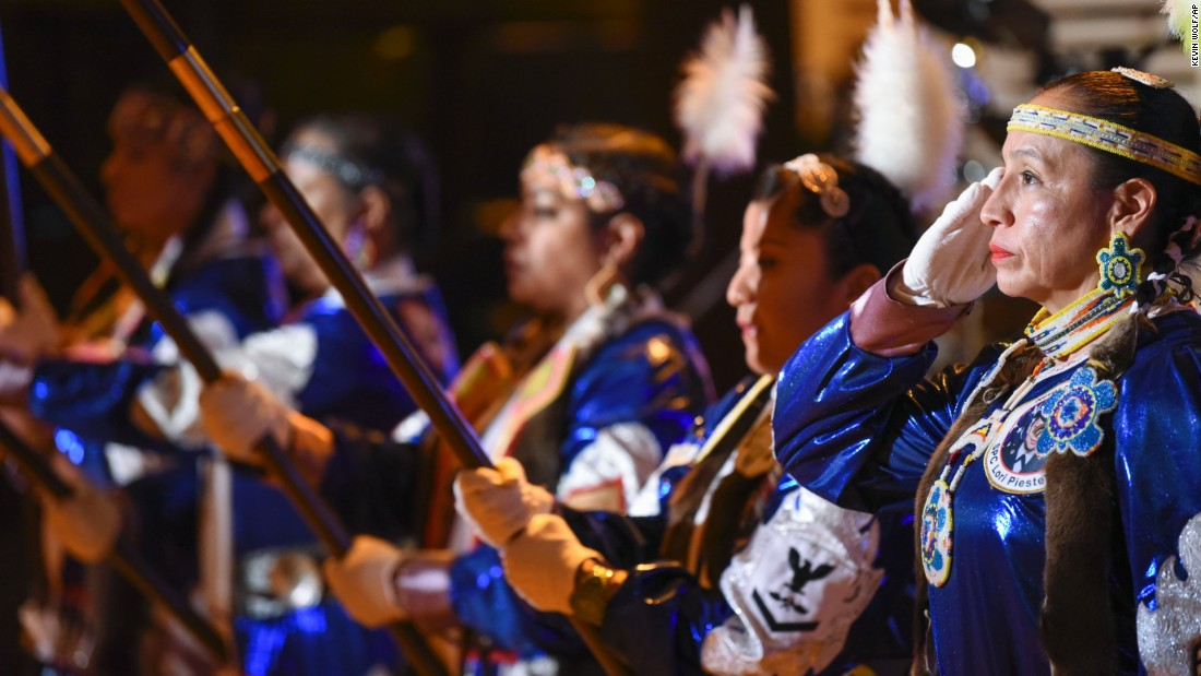 Mitchelene BigMan, right, president and founder of the Native American Women Warriors, salutes as the group performs the Presentation of Colors at the Native Nations Inaugural Ball at the Smithsonian's National Museum of the American Indian.