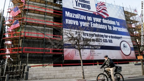 "A man cycles past a giant banner, bearing a message of congratulations (Mazeltov) for incoming US President Donald Trump, covering a building under construction in central Jerusalem on January 20, 2017. Outgoing US President Barack Obama warned his successor against any ""sudden, unilateral moves"" on the Israeli-Palestinian conflict, in an apparent reference to his plan to move the US embassy from Tel Aviv to Jerusalem. / AFP / Thomas COEX        (Photo credit should read THOMAS COEX/AFP/Getty Images)"